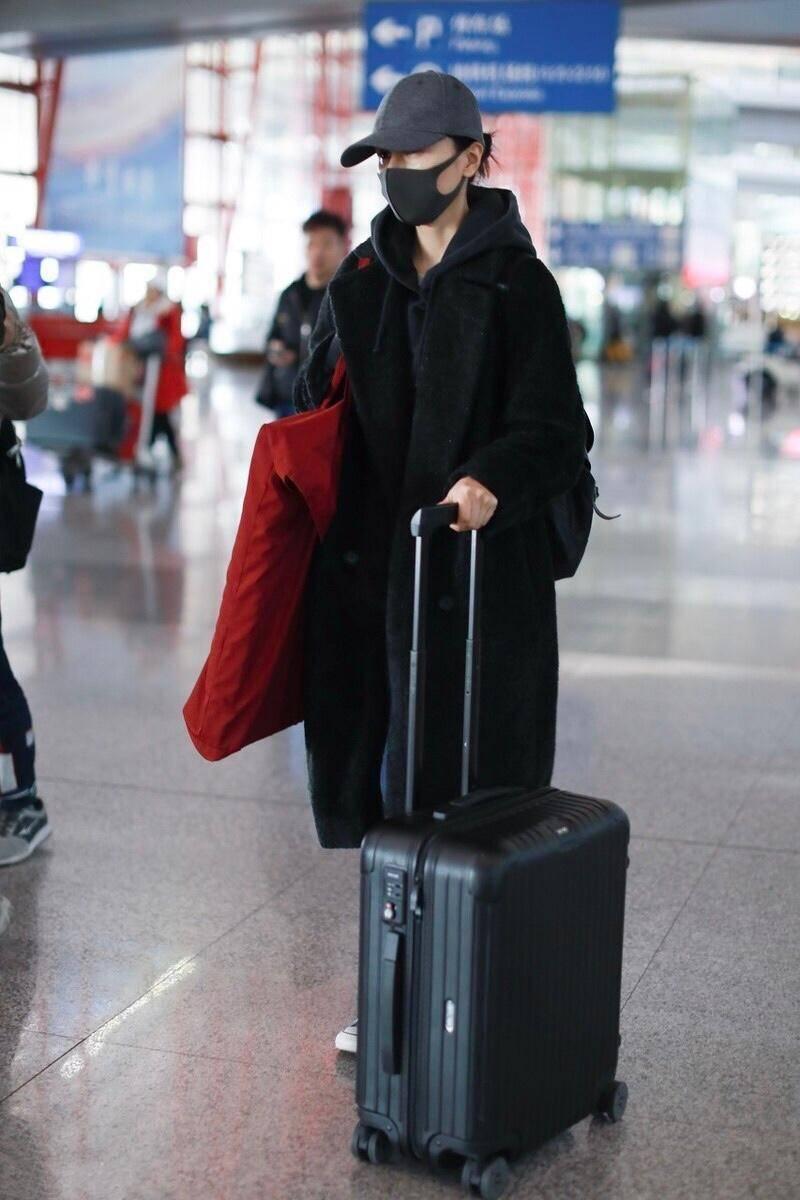 袁泉气场十足,穿一件黑色大衣内搭卫衣,结合牛仔裤走机场真洋气