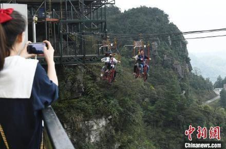 找刺激!重庆市民百米高空钢丝绳上骑自行车