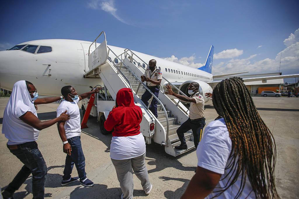 赢咖5首页海地非法移民遭美国遣返 落地后朝飞机扔石头鞋子泄愤
